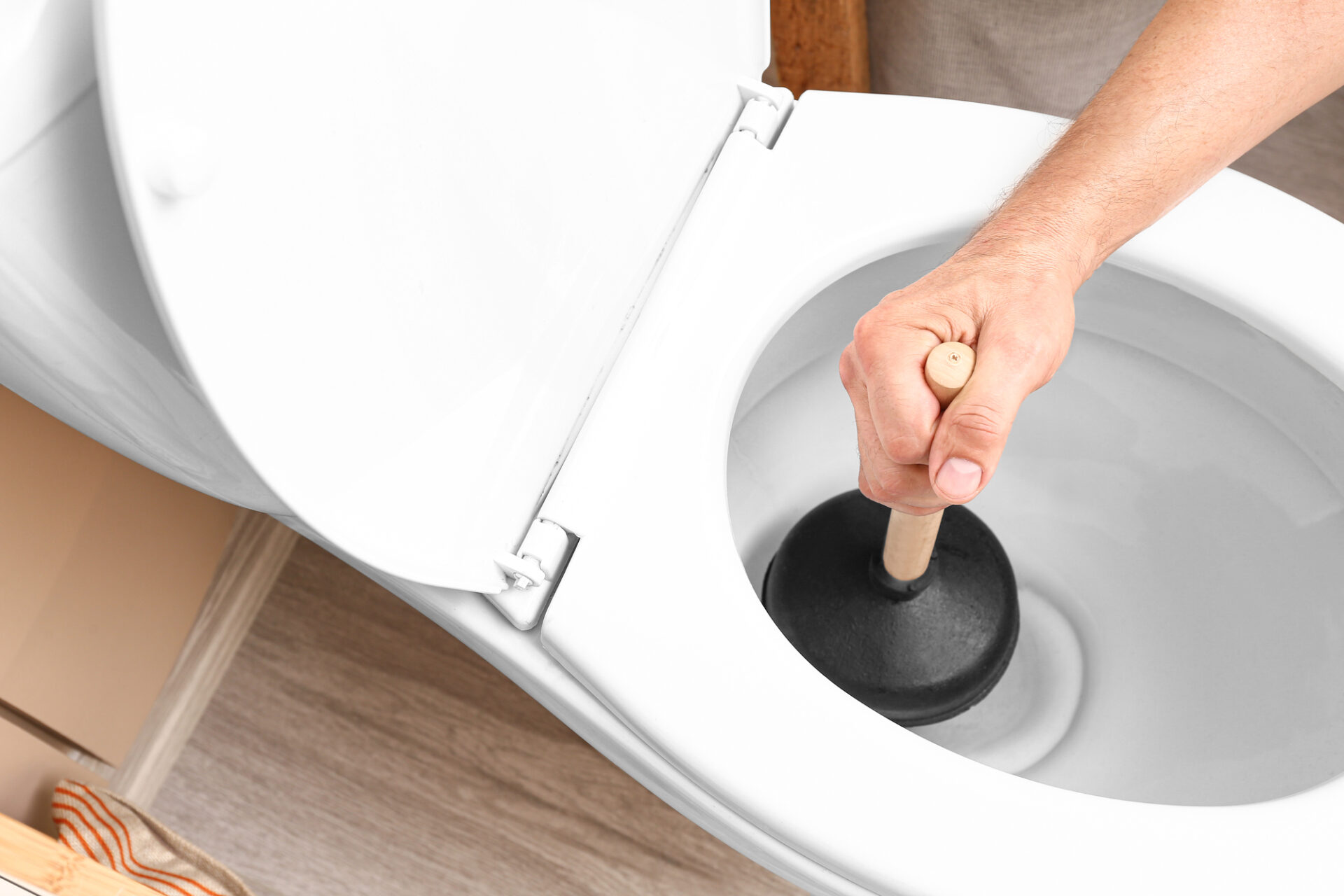 Man using plunger to unclog a toilet bowl
